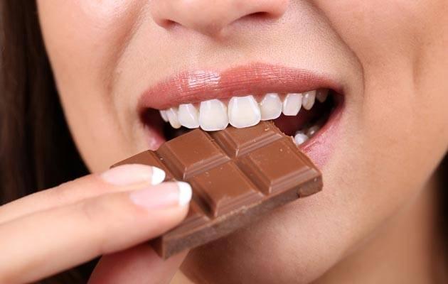 Женщина кушает шоколад