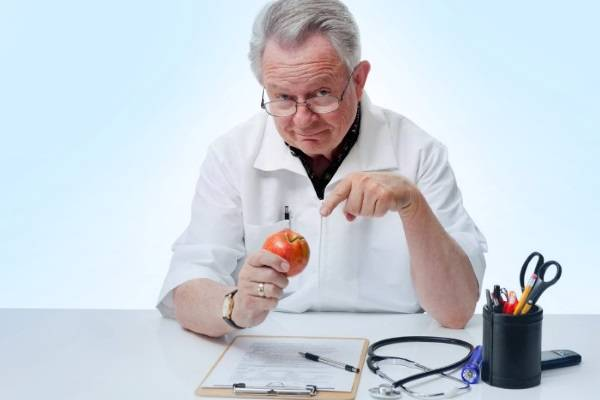 Доктор держит в руке красное яблоко