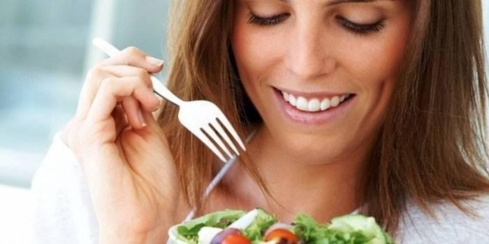 Девушка держит в руках тарелку с салатом и вилку