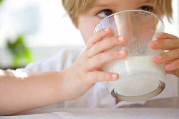 Малыш пьет молоко из стакана