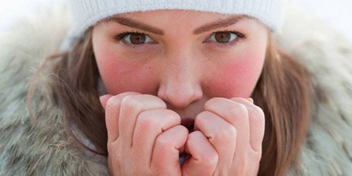 Девушка греет дыханием руки