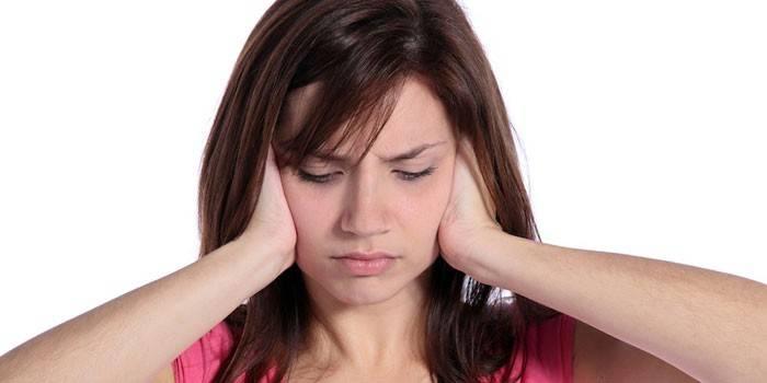 Девушка закрывает руками уши