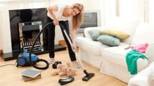 Девушка пылесосит в доме