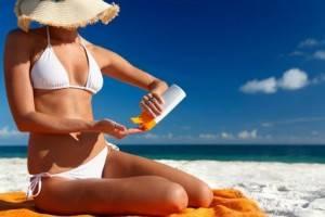 Девушка на пляже наносит крем от загара