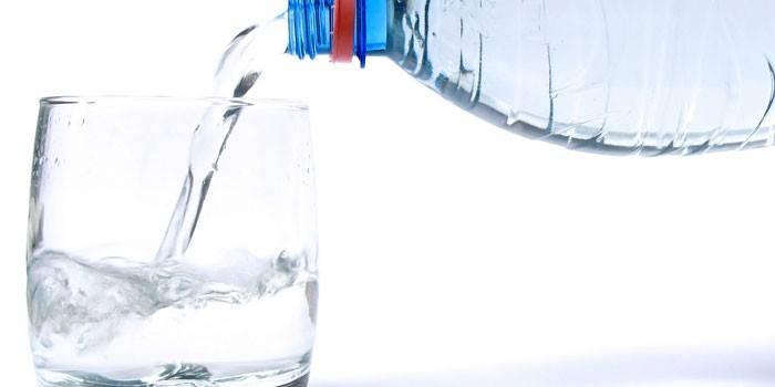 Воду наливают из бутылки в стакан