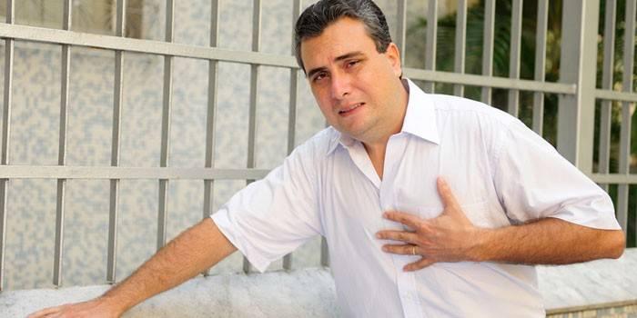 Мужчина держит руку в области сердца