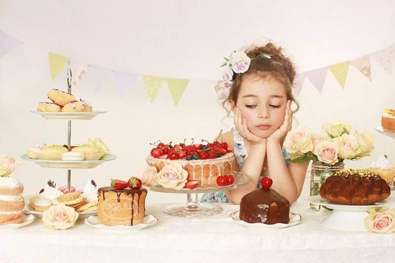 девочка сидит за столом среди тортов и пирожных