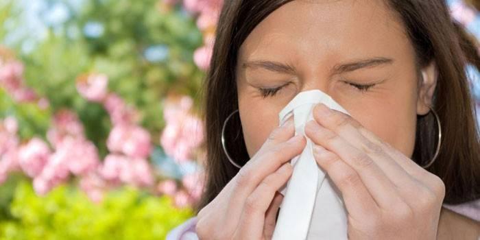 Девушка вытирает нос платком