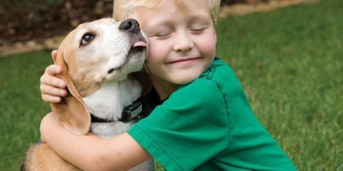 Мальчик обнимает собаку